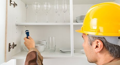 Pest control professional with flashlight checking kitchen shelf in Rochester