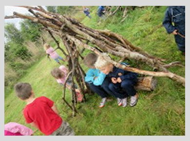 Children sitting in a wigwam they've made out of branches of wood