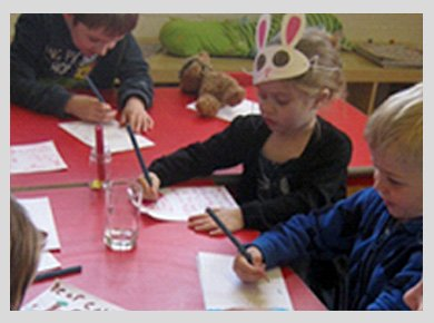 A little girl wearing a white and pink rabbit mask, sitting writing at a red table between two little boys