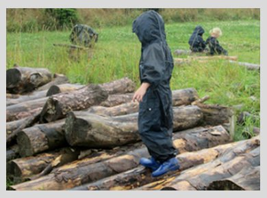 A little boy with his hood up, walking across a row of logs
