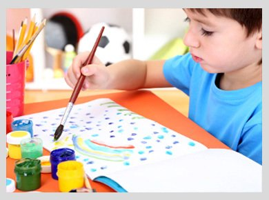 A little boy painting a picture with brightly coloured paints in small pots