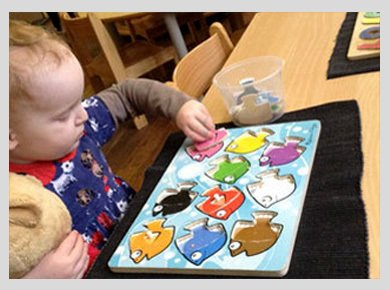A toddler playing with a shapes game, putting brightly-coloured fish into the right spaces