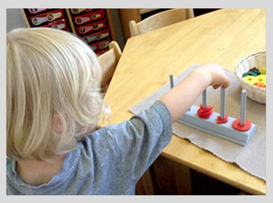 A little blonde child playing with a shape-sorter