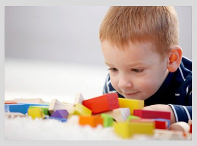 A little boy playing with coloured bricks