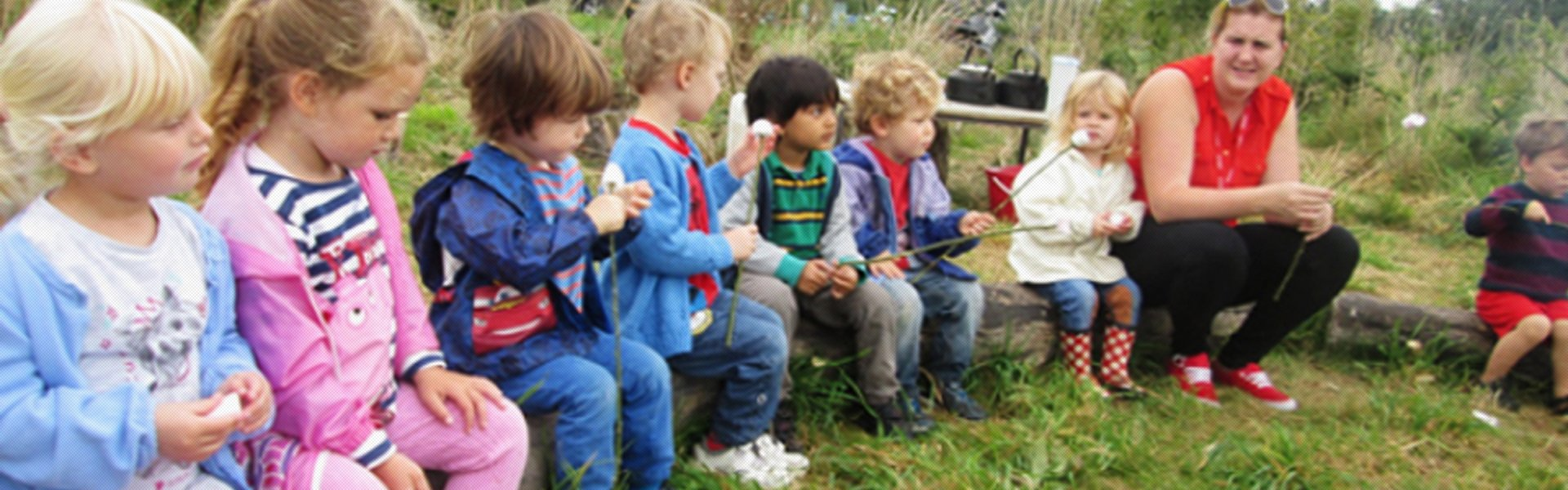 A row of children in outdoor clothes, sitting on a log with a carer
