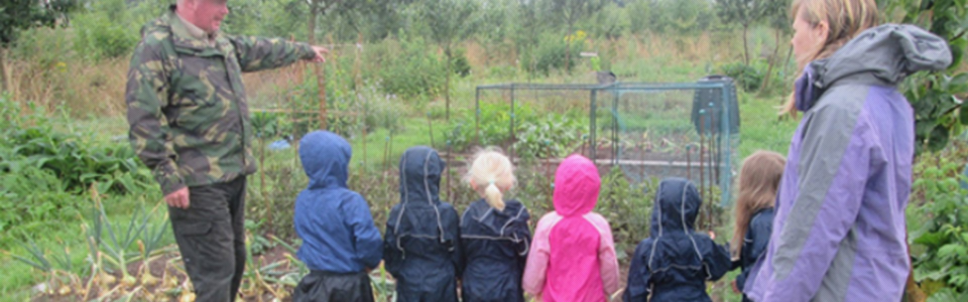 Children in outdoor clothes, in an outdoor area with a carer