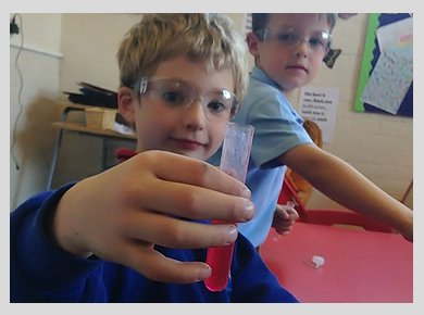 Two children wearing protective goggles, one holding up a test tube full of red liquid