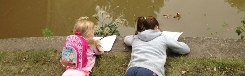 Two little girls lying on their stomachs beside a pond, making notes