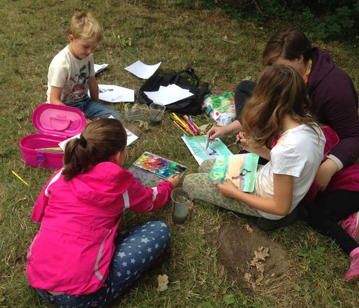 Children sitting in a circle on the grass, drawing and painting