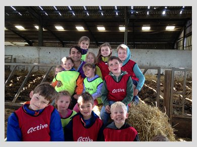 A group of children sitting on a haystack in a barn