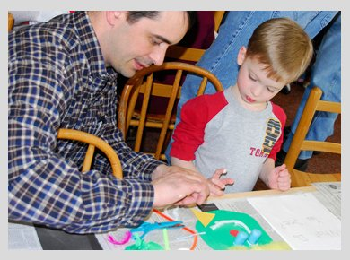 A man in a checked shirt, making a collage with a little boy