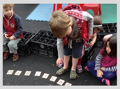 Children playing outside with numbered cards on the ground