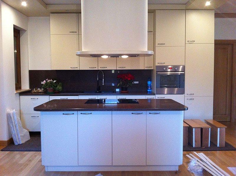 una cucina moderna con mobili bianchi e penisola con top di legno