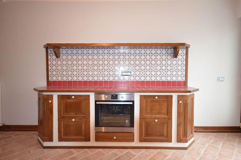 una cucina angolare con mobili in legno e di color bianco