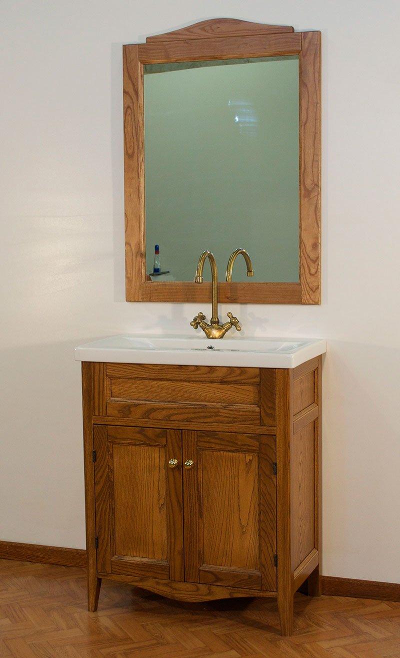 un mobiletto di legno e sopra un lavabo e uno specchio