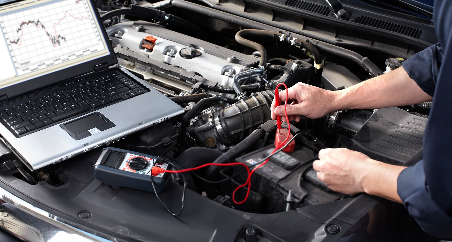 un meccanico con un computer portatile appoggiato sul motore di una macchina e un tester in mano