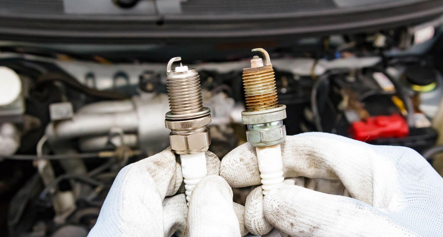 due mani con dei guanti bianchi e in mano due candele del motore