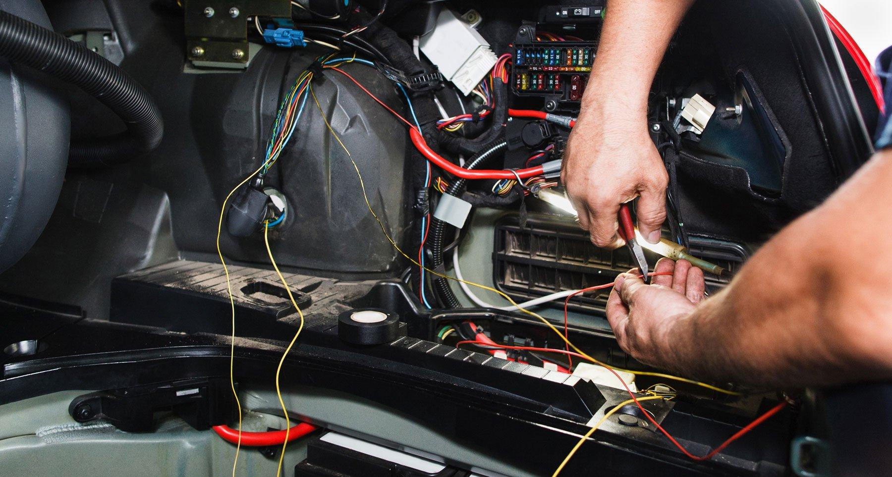 un elettrauto al lavoro all'interno dell'abitacolo di una vettura con cavi a vista