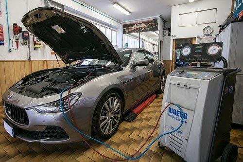 una Maserati grigia con il cofano aperto mentre ricarica l'aria condizionata