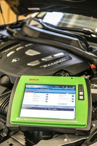 un apparecchio con monitor di color verde per test diagnostici appoggiato su un motore di una macchina
