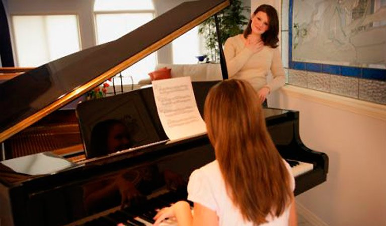 Mother watching daughter play piano