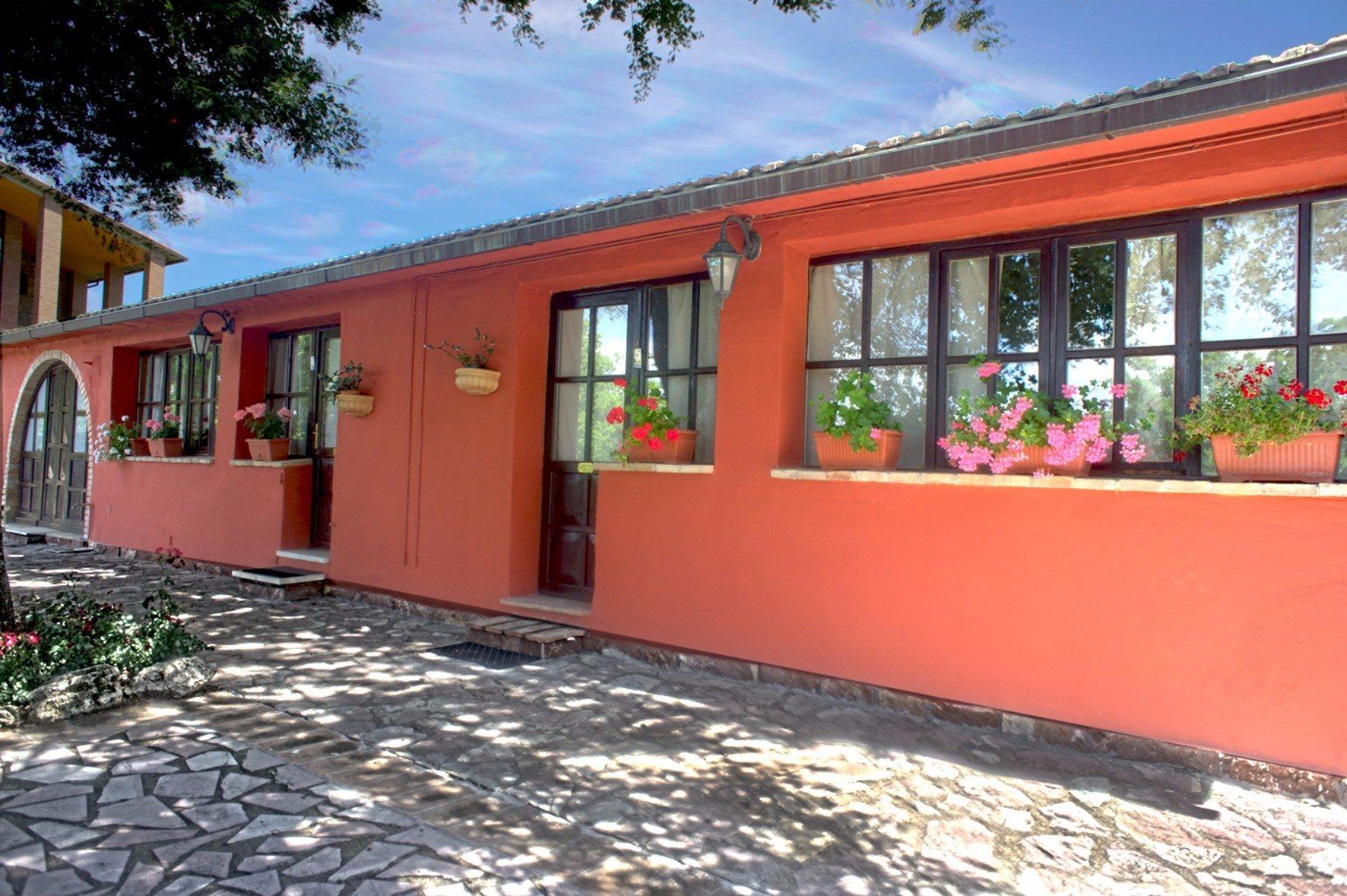 un edificio rosso con vasi di fiori alle finestre