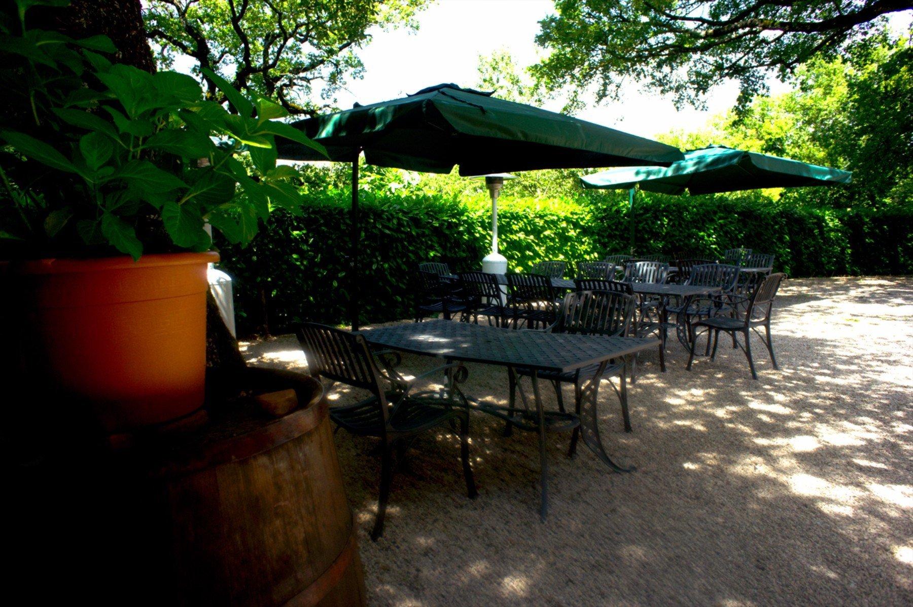 dei tavoli sotto a  degli ombrelloni verdi