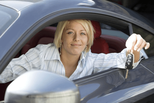 Woman with car key at auto driving school in Rochester, NY