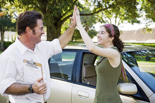 Auto driving school trainer and student doing high five in Rochester, NY