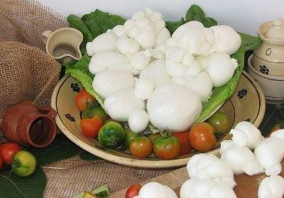 un piatto con dei pomodorini, delle mozzarelle su un letto di insalata e accanto altra verdura