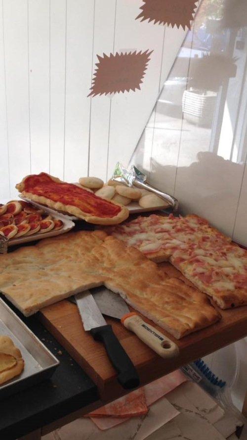 dei tranci di focaccia e delle pizze su un tagliere