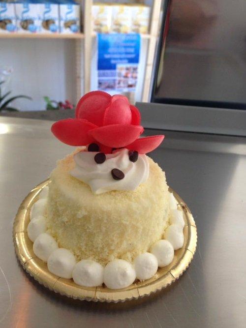 una torta con delle meringhe, pezzetti di cioccolato e dei fiori rossi gluten free