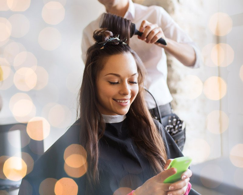 brunette lady looking at phone while getting her hair done