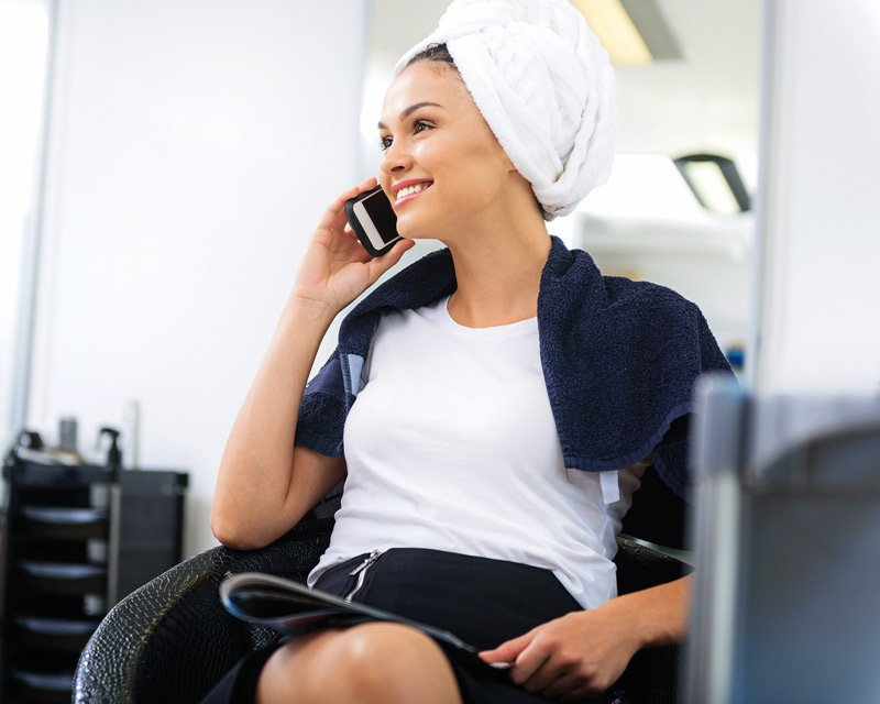 lady in salon with towel on her head talking on the phone