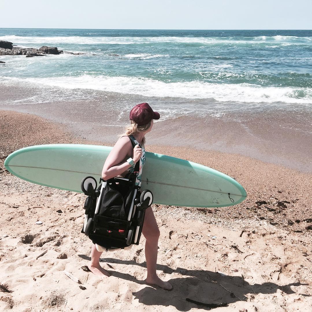 donna con nave e passeggino alla spiaggia