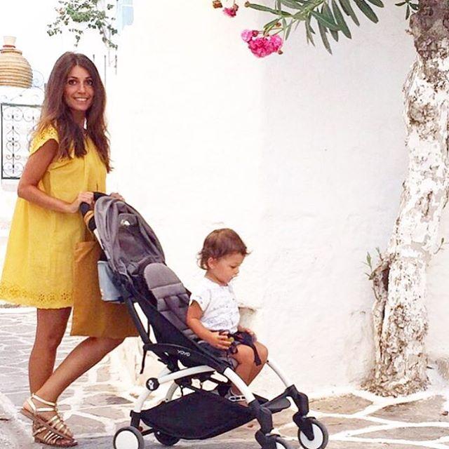 donna posa per una foto con bambino seduta su un passeggino