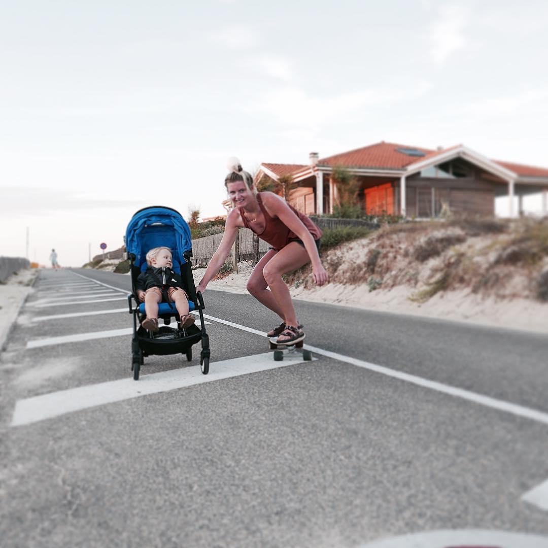 donna con bambino seduta su un passeggino sulla strada