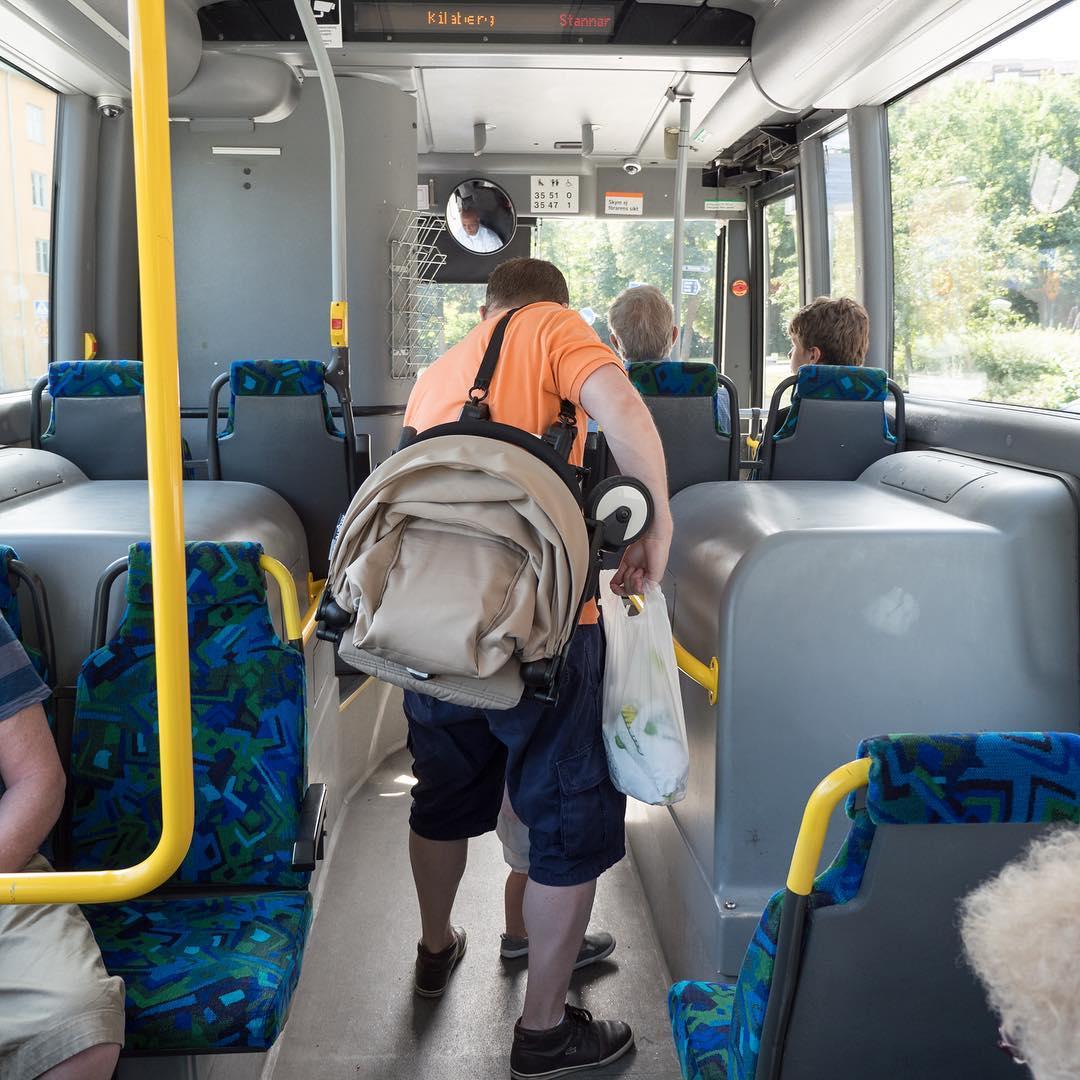 Uomo che tiene il passeggino sulla spalla con bambino in autobus