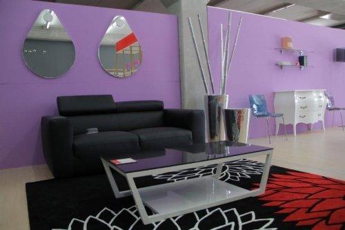 Moderna sala di stare con originali specchi sotto forma di lacrima,tappeto tricolore nera,bianca e rossa,nel fondo originale cassettiera bianca