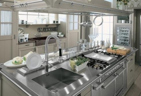 Cucina di legno con tutti gli elettrodomestici di acciaio e un tavolo di lavoro centrale per sognare