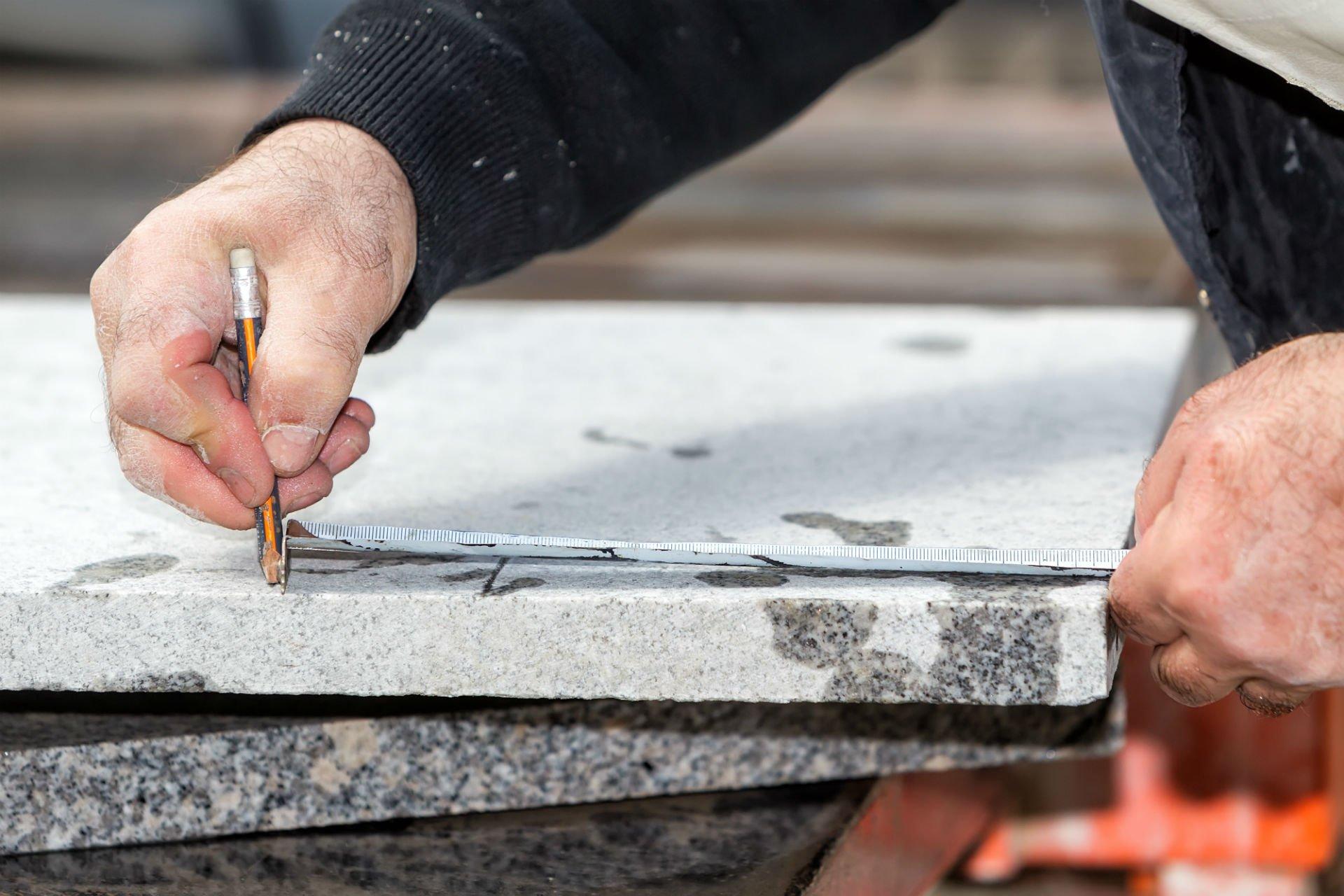 una mano con una matita che prende una misura di una lastra di marmo