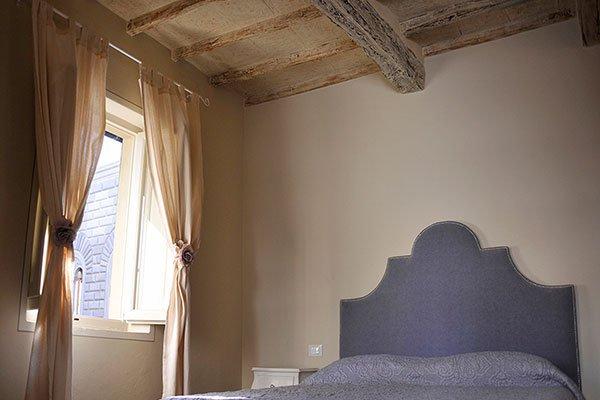il tetto della camera da letto é di legno con travi