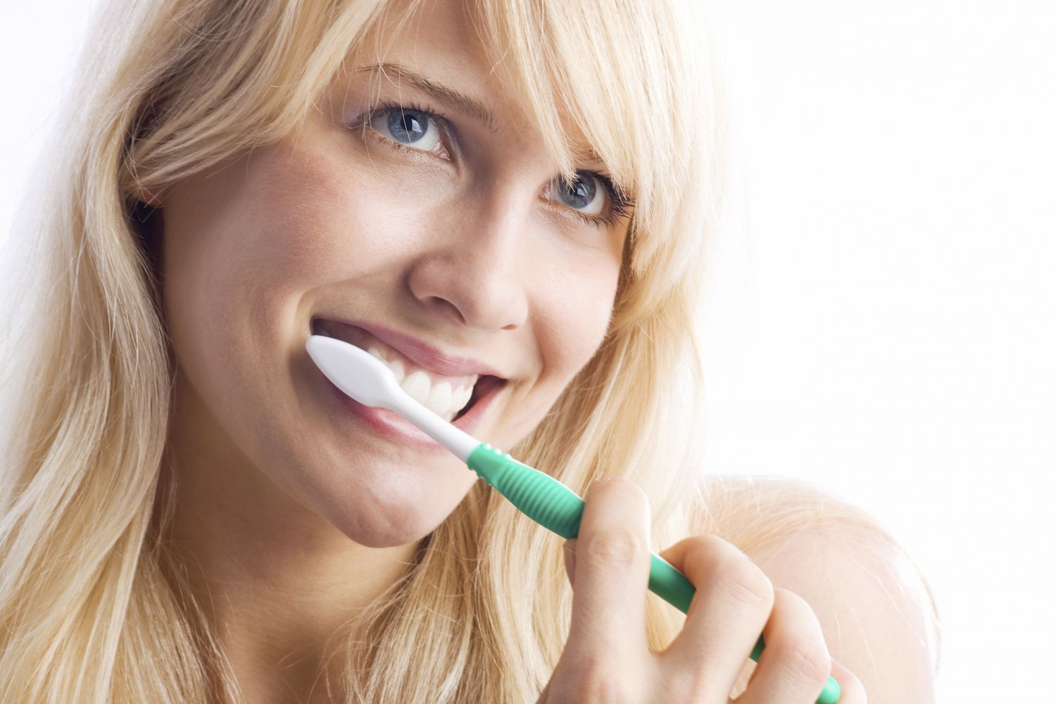 Pretty young woman brushing her teeth
