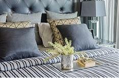 un letto con un copriletto a righe e dei cuscini di color grigio