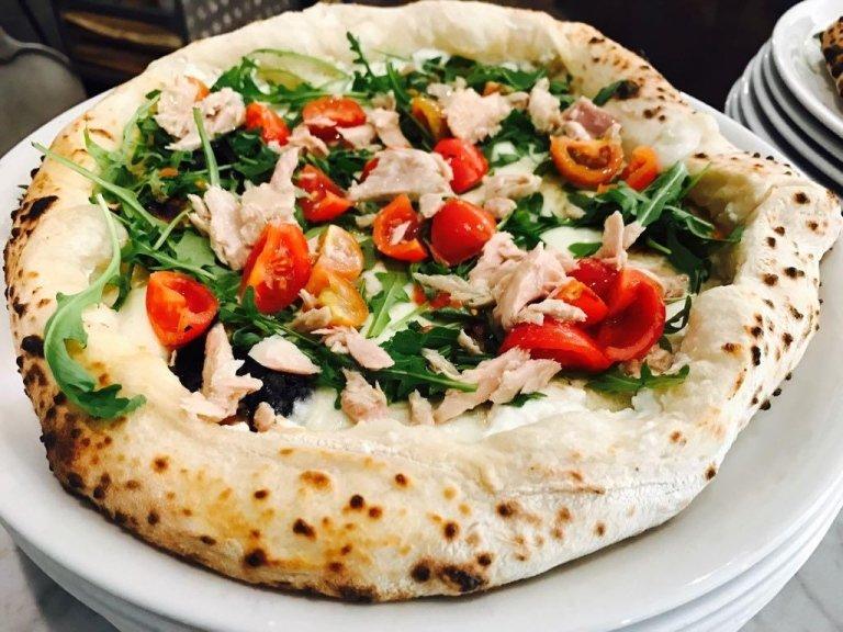 Pizza con cornicione ripieno di ricotta di bufala, tonnetto alletterato del Mediterraneo, pomodorini ciliegini, rucola, fior di latte di Agerola e olio extravergine d