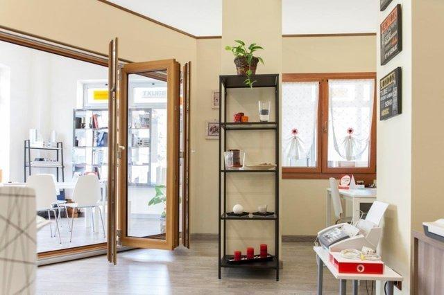 vista interna di una casa con una scaffale, finestra in legno, porte in vetro e arredamenti