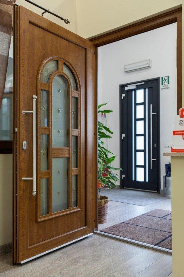 vista di una porta in legno con anta aperta e porta nera con arredamenti di casa