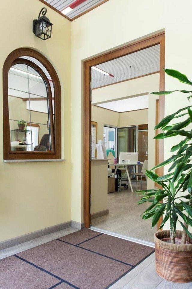 vista angolare di una casa interna con parete gialla, finestre in alluminio e porta senza ante
