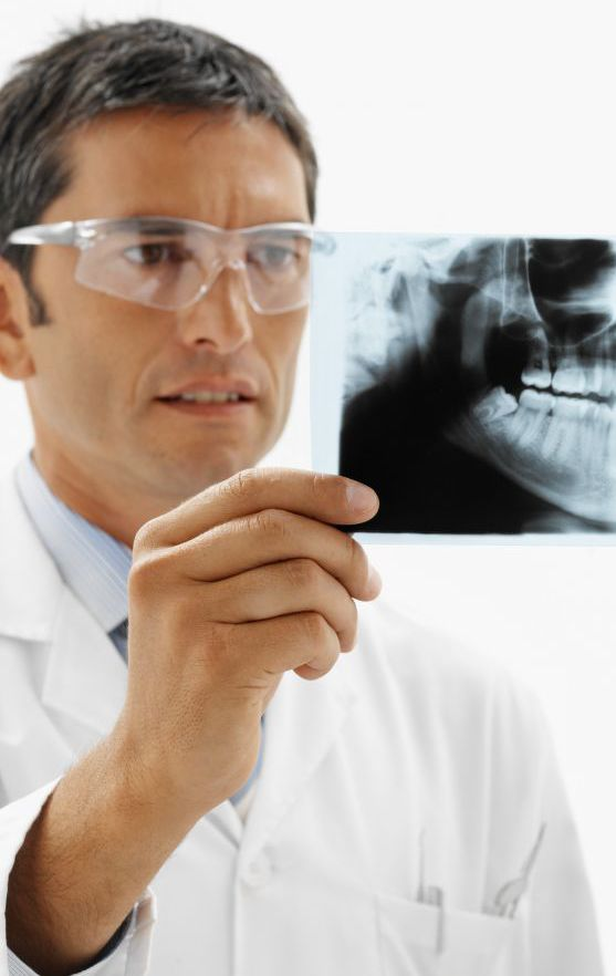 Dentist examining an x-ray to provide good oral hygiene in Winder, GA