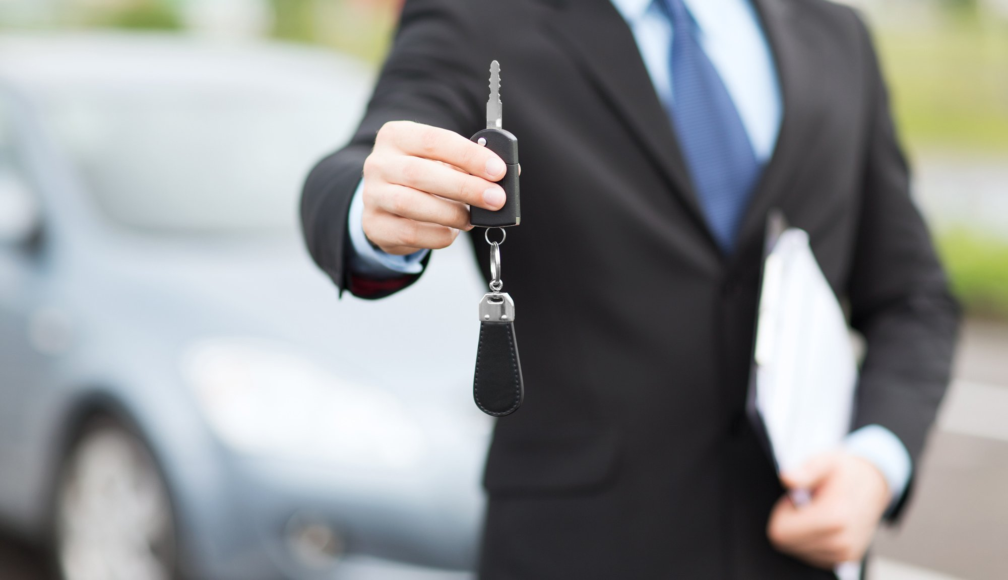 Car dealer handling key of car after approving auto loans in Richmond